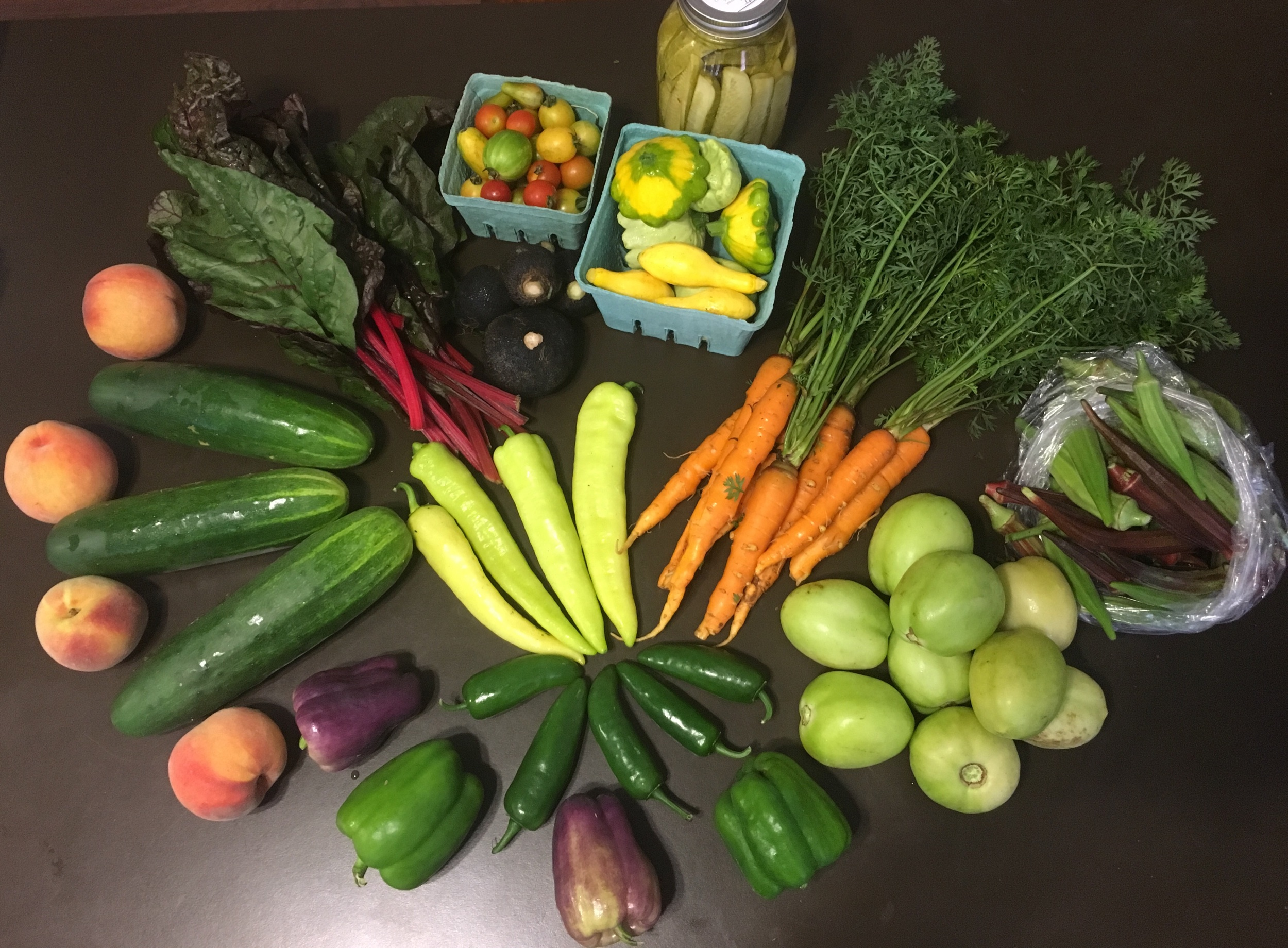 Peaches, slicing cucumbers, Swiss chard, black radishes, cherry tomatoes, assorted squash, pickles, carrots, okra, banana peppers, jalapeños, purple and green bell peppers, green tomatoes.