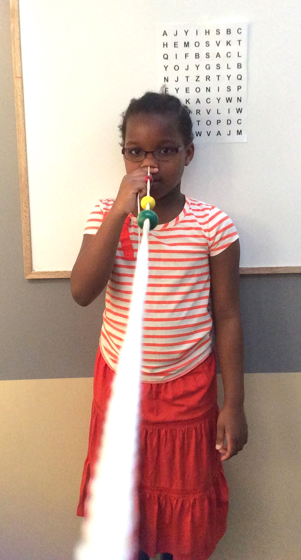 This is Grace doing a vision therapy exercise called the brock string, alternating her focus betweendifferent objects on the string.