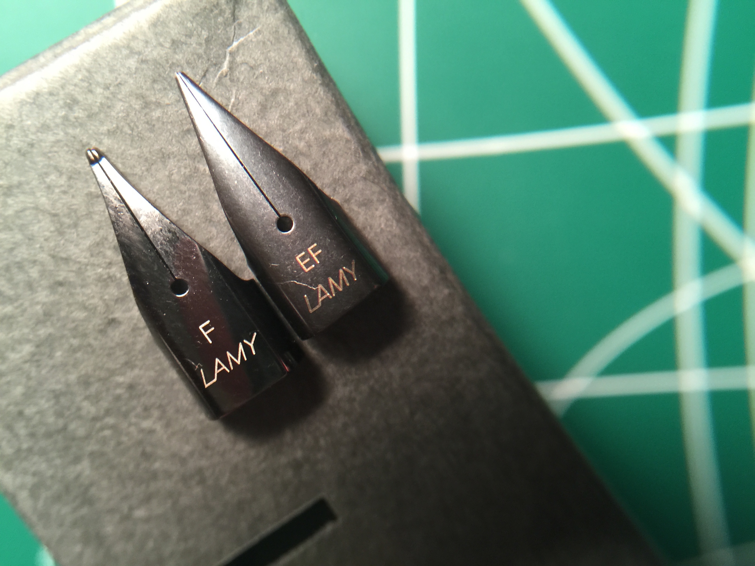 "Left: Counterfeit Fine nib; Right: Legitimate Extra-Fine nib.  Notice the nib slit on the counterfeit is off center from the breather hole; the left tine is longer than the right one, and the breather hole is farther forward.  The stamped nib size and ""Lamy"" name are in a different ink color as well."