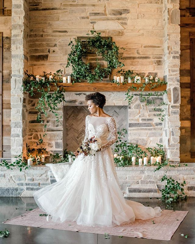 Dreamin' by the fire✨ How gorgeous is this gown on @hellolaurentaylor_ (look at that neckline). Loving how some simple greenery and candles transformed this fireplace into a warm and dreamy space! What adorns your mantle for the holidays? . . .  Venue // @stonecrestvenue Photography // @graydoorphotography Floral Design // olivegrovedesign  Beauty // @beautybyyari Rentals // @beautiful_event_rentals Cake // @crumbandkettle_dfw Stationery // @mca_designs Dress // @lovelybridedallas @lovelybride Jewelry // @thetruegemcompany Vintage Car // @bluediamondlimousines_of_tx Holiday Platter // @figandgoat Model // @hellolaurentaylor_  Planner // @lyonsevents