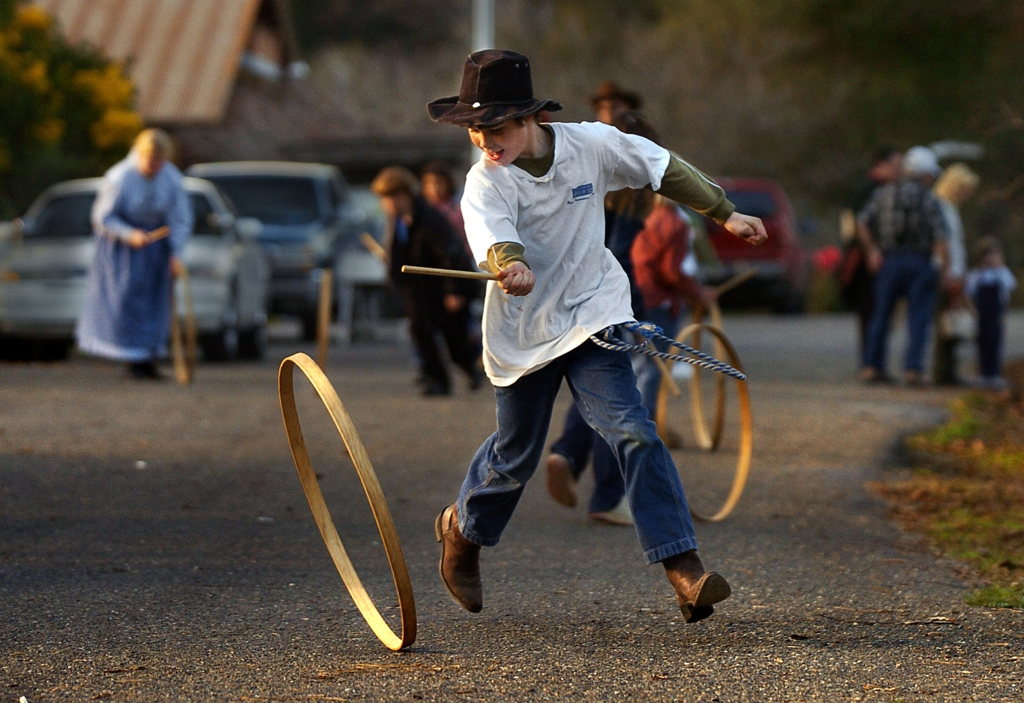 Philip Cowdery 9 rolls a wooden hoop down the road at the 'Christmas In Coloma' festival at the Marshall Gold Discovery State Park in Coloma on Sunday December 12, 2004.