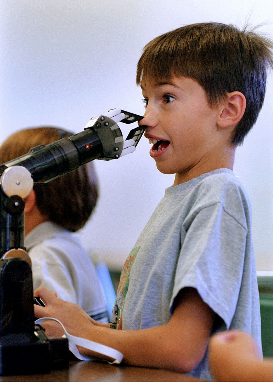 """Jason Kaye 9, pinches his nose in the grip of a mechanical robotic arm at the R.G. Smith Clubhouse in Folsom on Thursday July 25, 2002. """"Mad Scientist"""" Jason Turner put on a science class themed """"Machine Mania"""" and featured simple machines."""