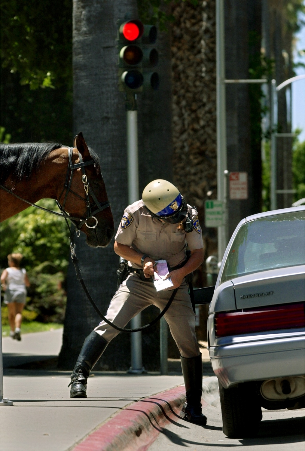 """CHP Officer Tony Pineiro issues a traffic citation to a motorist who was driving on L street near the State Capitol in Sacramento on Thursday July 3, 2003. Pineiro pulled the driver over from his patrol horse named """"Bo."""""""