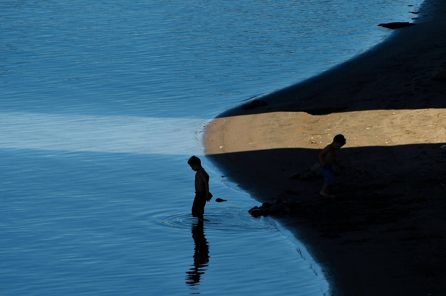A young boy wades into the shallow water of the American River beneath the twin spans of the I-5 bridge at Discovery Park in Sacramento on Thursday, June 6, 2013.