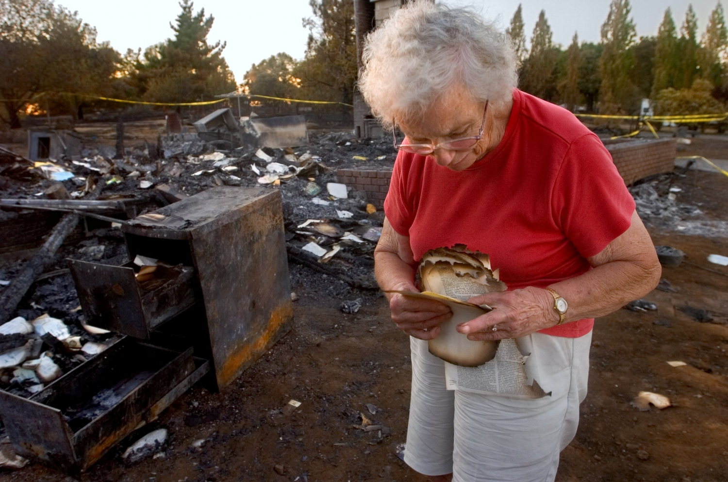 Edith Hoffman picks through the ashes of her home in El Dorado on Wednesday July 19, 2006 after it was destroyed by a wild fire.