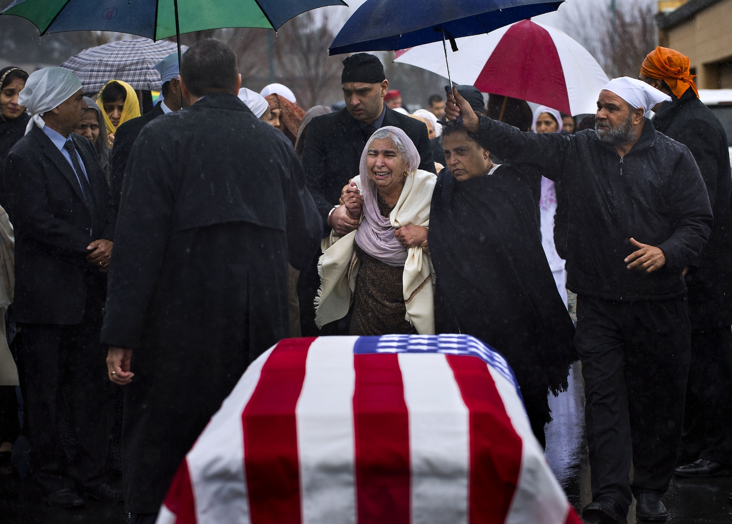 Sukhwinder Kaur, center, is escorted past the flag-draped casket of her son Parminder Singh Shergill at Cherokee Memorial Park in Lodi on Saturday, February 8, 2014. Parminder Singh Shergill was a US Army veteran and was shot to death by police in Lodi.