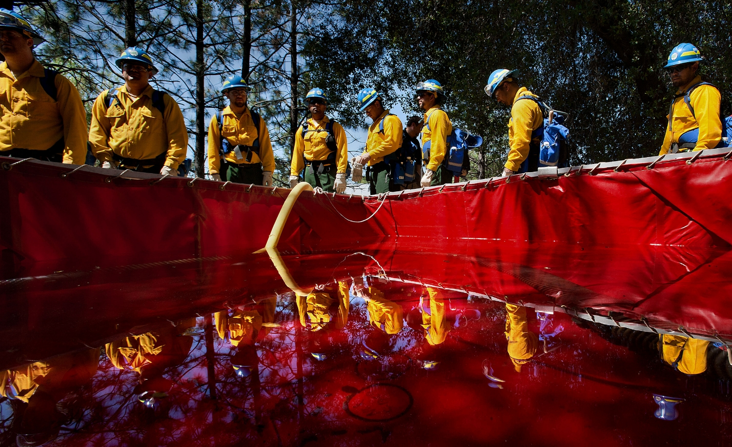 Firefighters line up around a makeshift water tank during a training exercise at the California Conservation Corps facilities in Auburn on Wednesday, May 9, 2012.