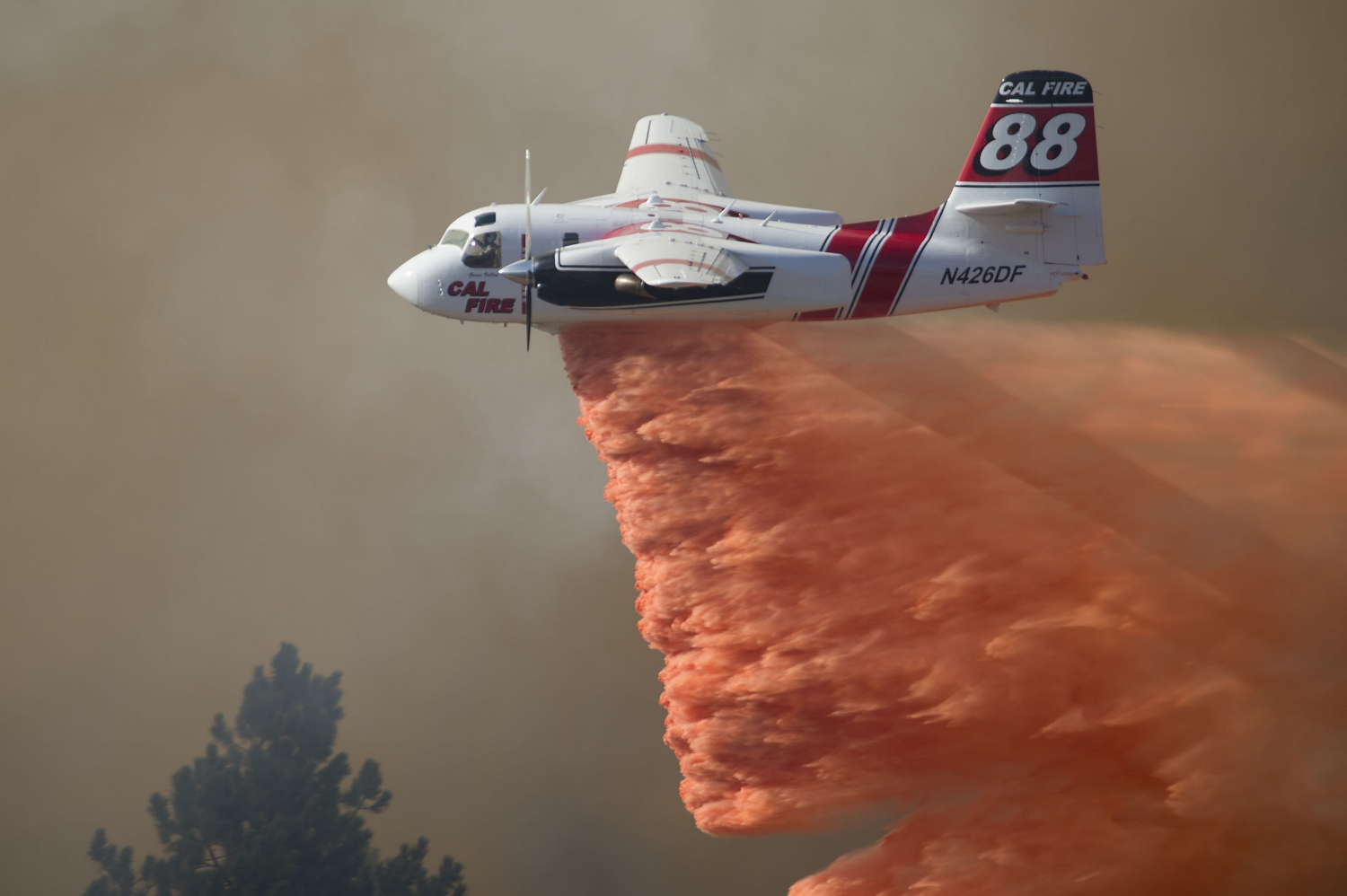 A Cal Fire aircraft drops fire retardant on a wild land fire burning near the Story winery in Plymouth, CA on Friday, July 25, 2014.