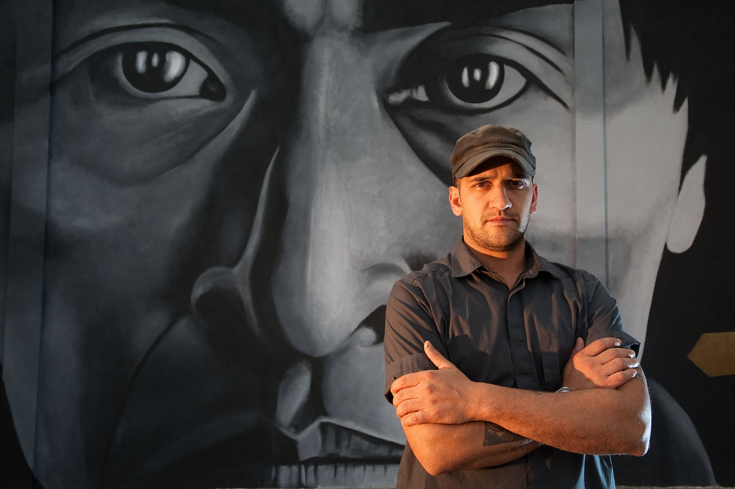 Mural artist Alex Forster stands in front of his artwork at 24th Street and Broadway in Sacramento on Monday, April18, 2011.
