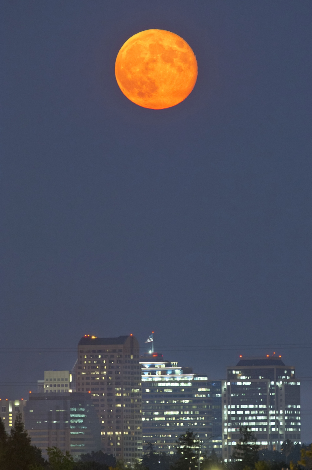 """The """"Supermoon"""" rises over the Sacramento skyline on Tuesday, September 9, 2014. When the moon's orbit brings it closest to Earth, or perigee, when it is full it is called a """"Supermoon."""""""