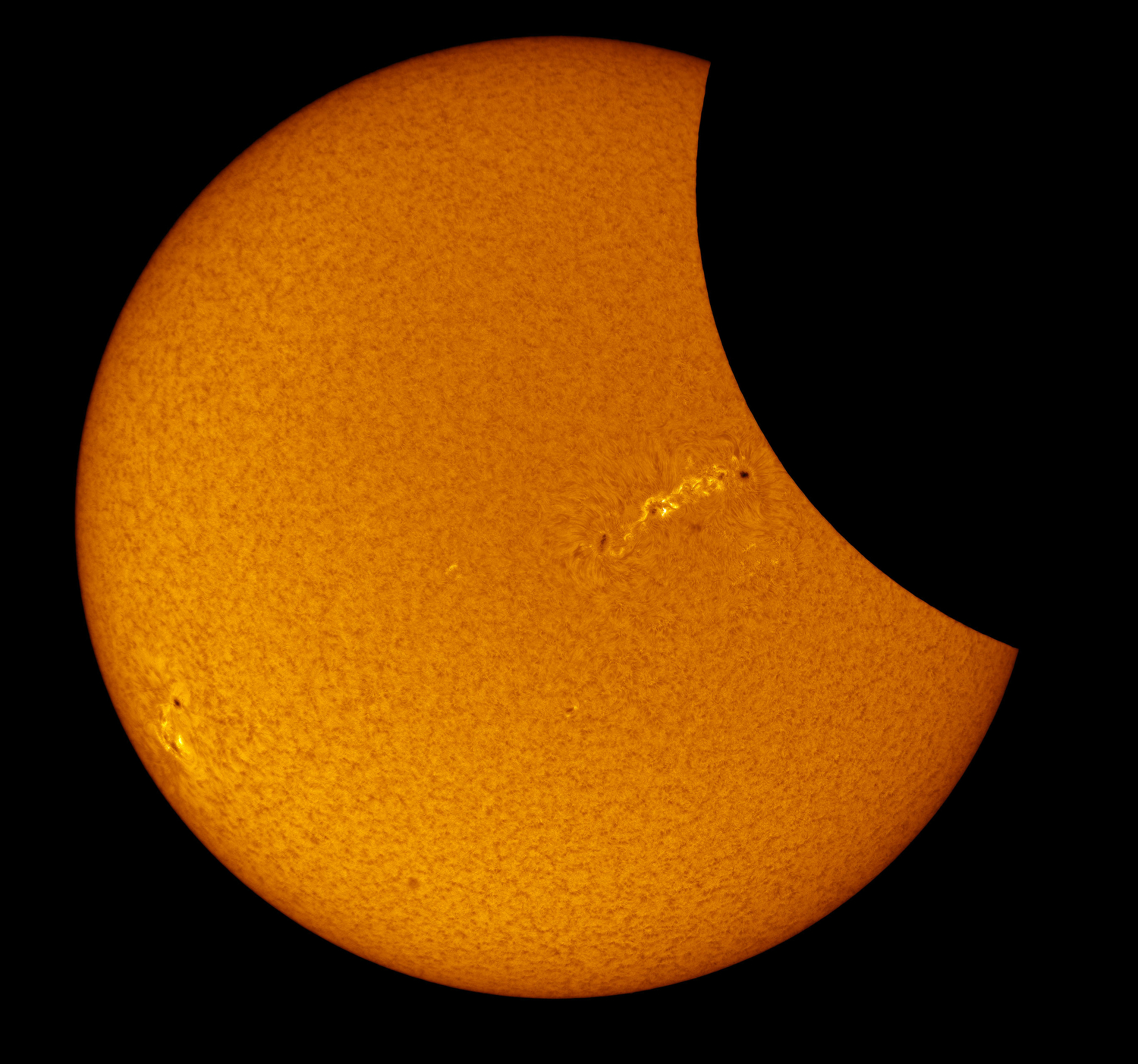 In this image in Hydrogen-alpha light derived from video and in false color, sunspot activity is clearly visible as the moon partially obscures the sun during the total solar eclipse near Mitchell, OR on Monday, August 21, 2017.