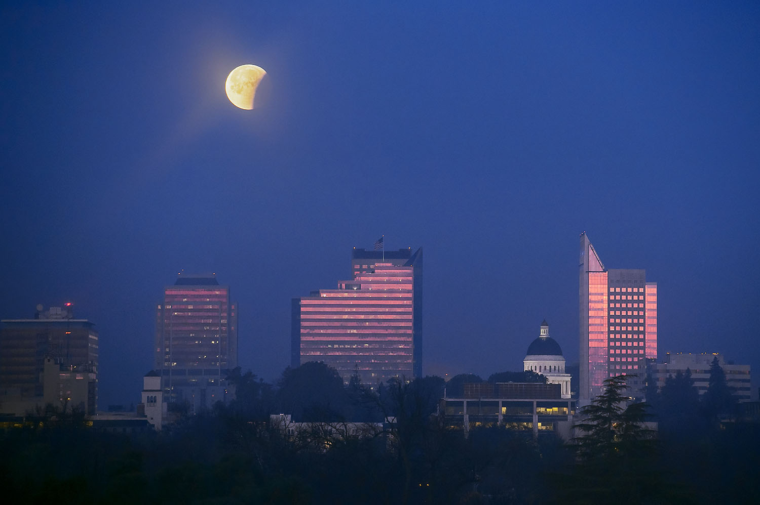 """The partially eclipsed moon is seen through a thin veil of morning fog over the skyline of Sacramento on Wednesday, January 31, 2018. This morning's total lunar eclipse coincided with a """"blue moon"""" and a """"super moon."""""""
