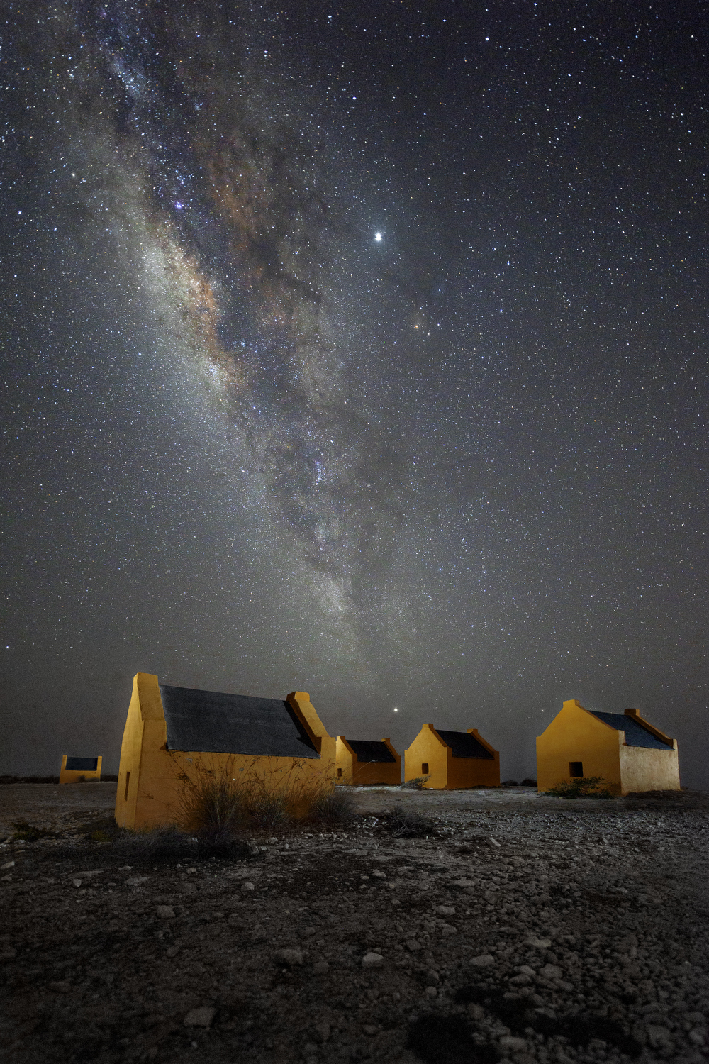 The Milky Way arches above the red slave huts on the southern tip of Bonaire, Friday, July 26, 2019. The four-foot high huts were built in the 1850s, and are a remnant of a time when Dutch colonists used slave labor to extract salt from sea water on the south end of the island.