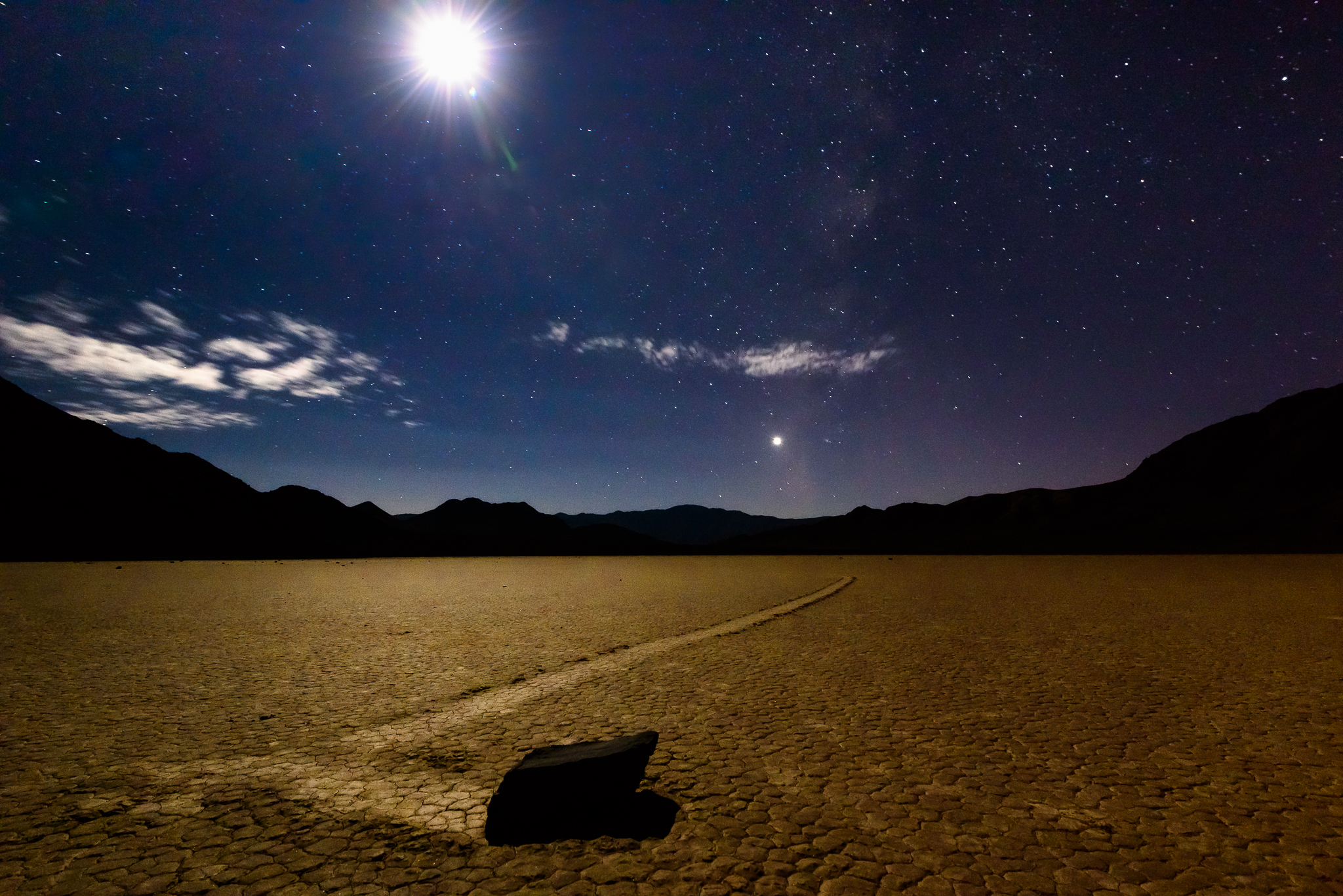 A quarter moon rises above the moving rocks of Death Valley's Racetrack,