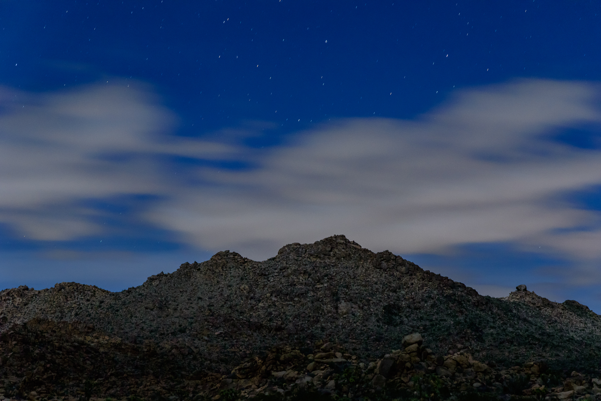 Moonlight dances between revealing and hiding layers of earth. Joshua Tree National Park, CA.