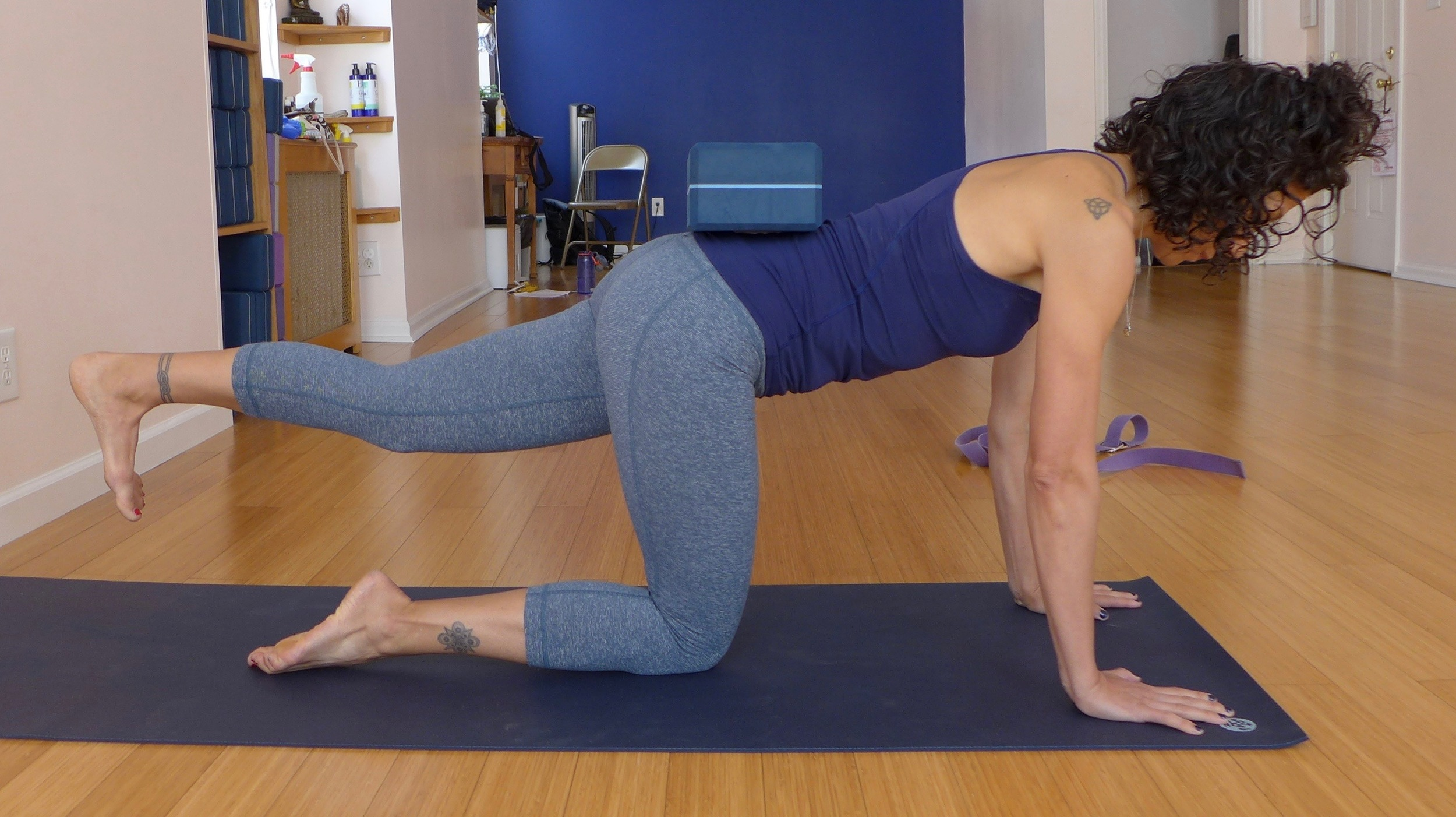 Opposite leg balance, elevated leg: Once you're stable in your pelvis, elevate the back leg. Stay out of external rotation of the elevated leg, keeping the hip points level. Focus on full hip extension and bracing the abdominal wall. Let the block inform you of where your pelvis is in space.  Hold for five breaths, then change sides.
