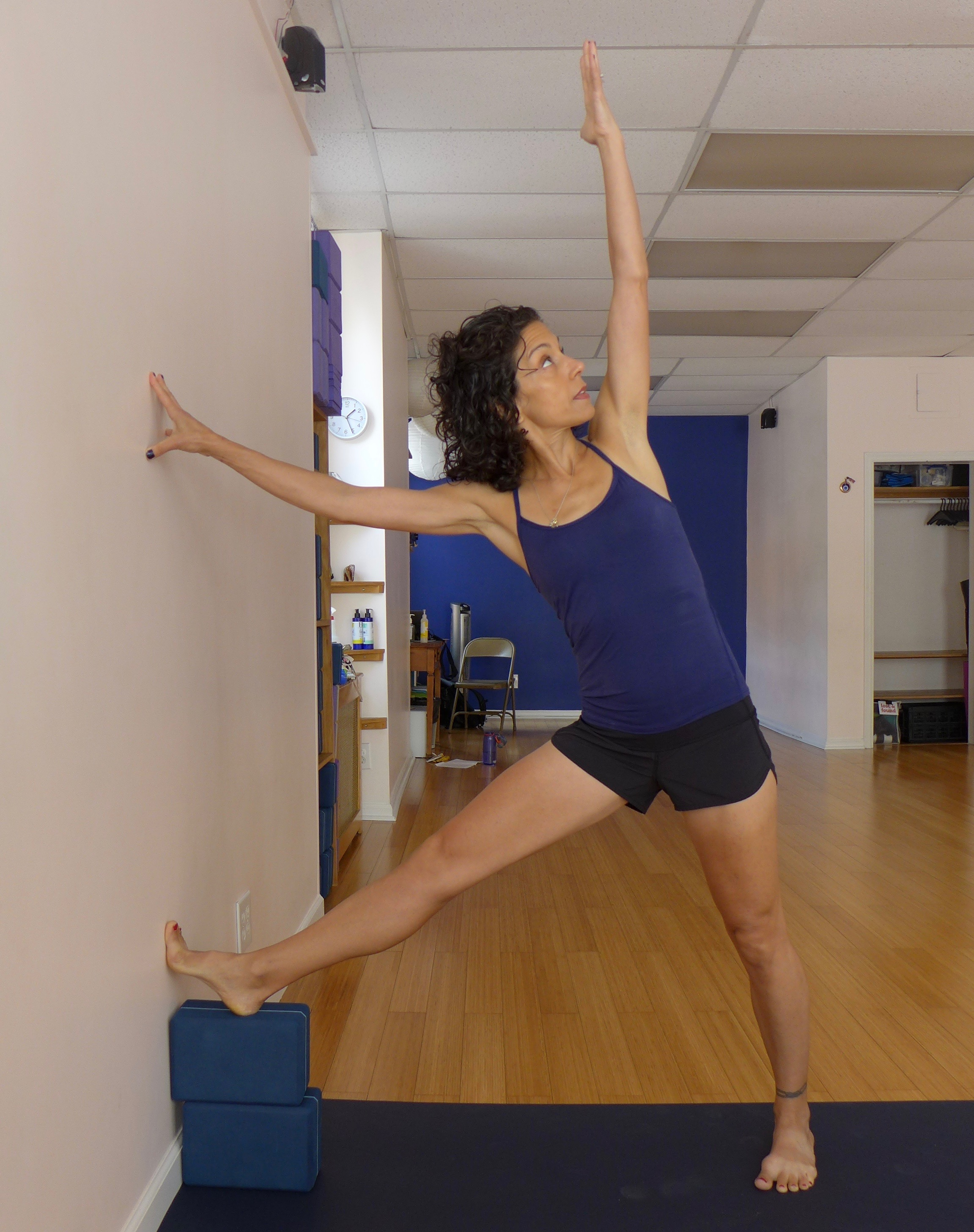 Triangle variation, using the wall and blocks. Stack two blocks against the wall. Make sure the blocks are on a secure surface. Place your right toes up the wall and your right heel on the block. Both quadriceps are engaged to prevent knee locking. Press into the wall with your right fingertips and toes - pressing into the wall creates resistance, and this resistance creates pelvic stability. Reach up towards the ceiling and over towards the wall with your left arm. This version of triangle helps to reset the right thighbone in the socket, and provide more length in the left side waist. Hold for five to seven breaths, then repeat on the left side.