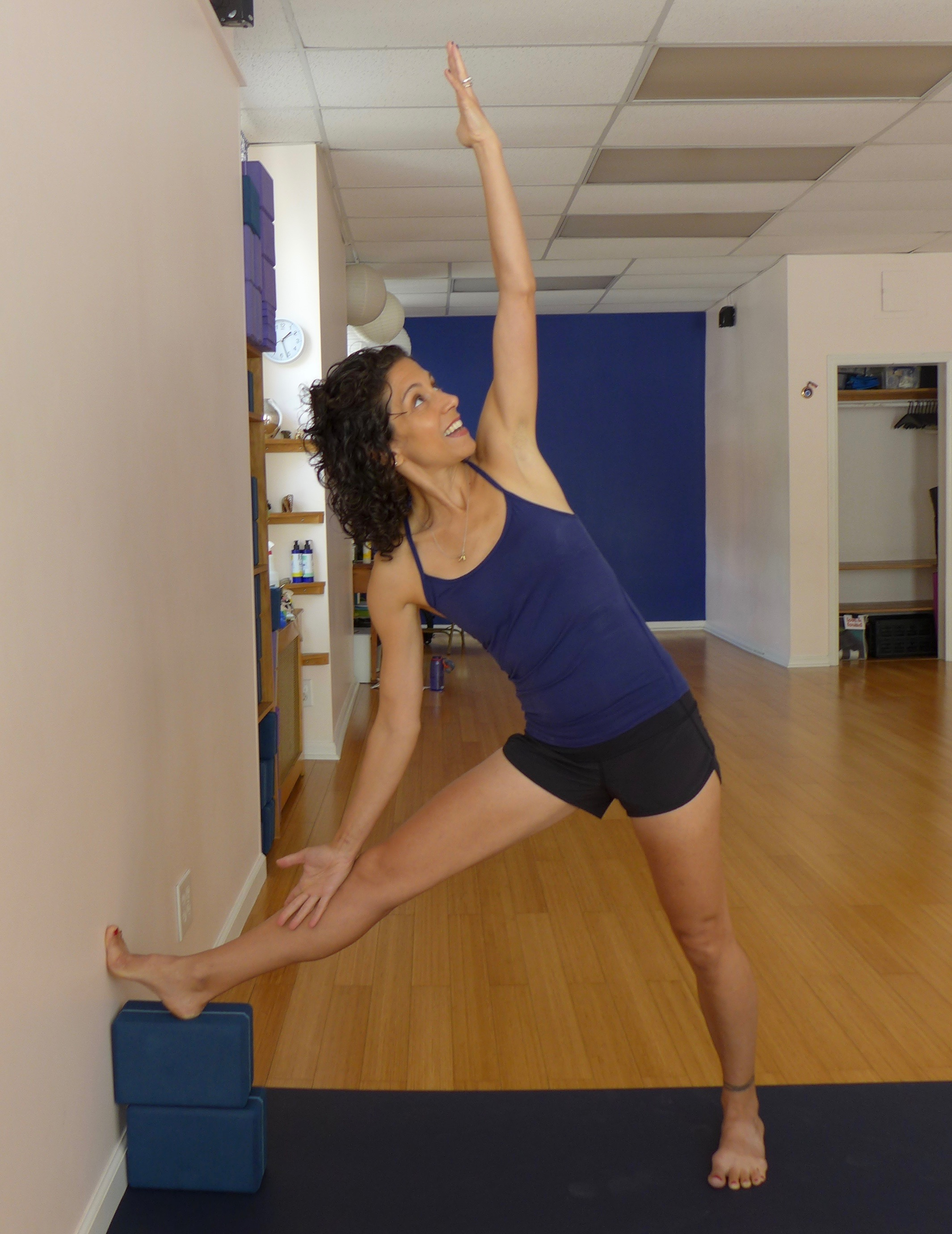 Triangle variation with wall and blocks, Part 2: If you feel stable in the version above, then try placing your hand on your thigh or shin.