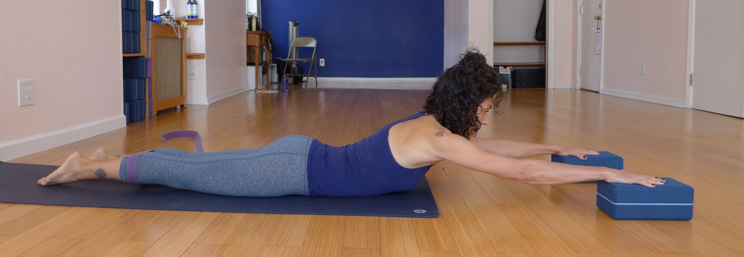 Cobra pose variation: This version of cobra helps to train full hip and spinal extension, as well posterior tilt of the pelvis.. Strap your shins like you did in mountain pose at the beginning of the practice, then press out into the strap. This will help engage the lower glutes and outer hips to secure the pelvis into a posterior tilt. Firmly press your hands down into the blocks. Keep your feet on the ground and lengthen your chest towards the blocks, like you did in cow pose.  Hold for five breaths, release, then repeat two more times.