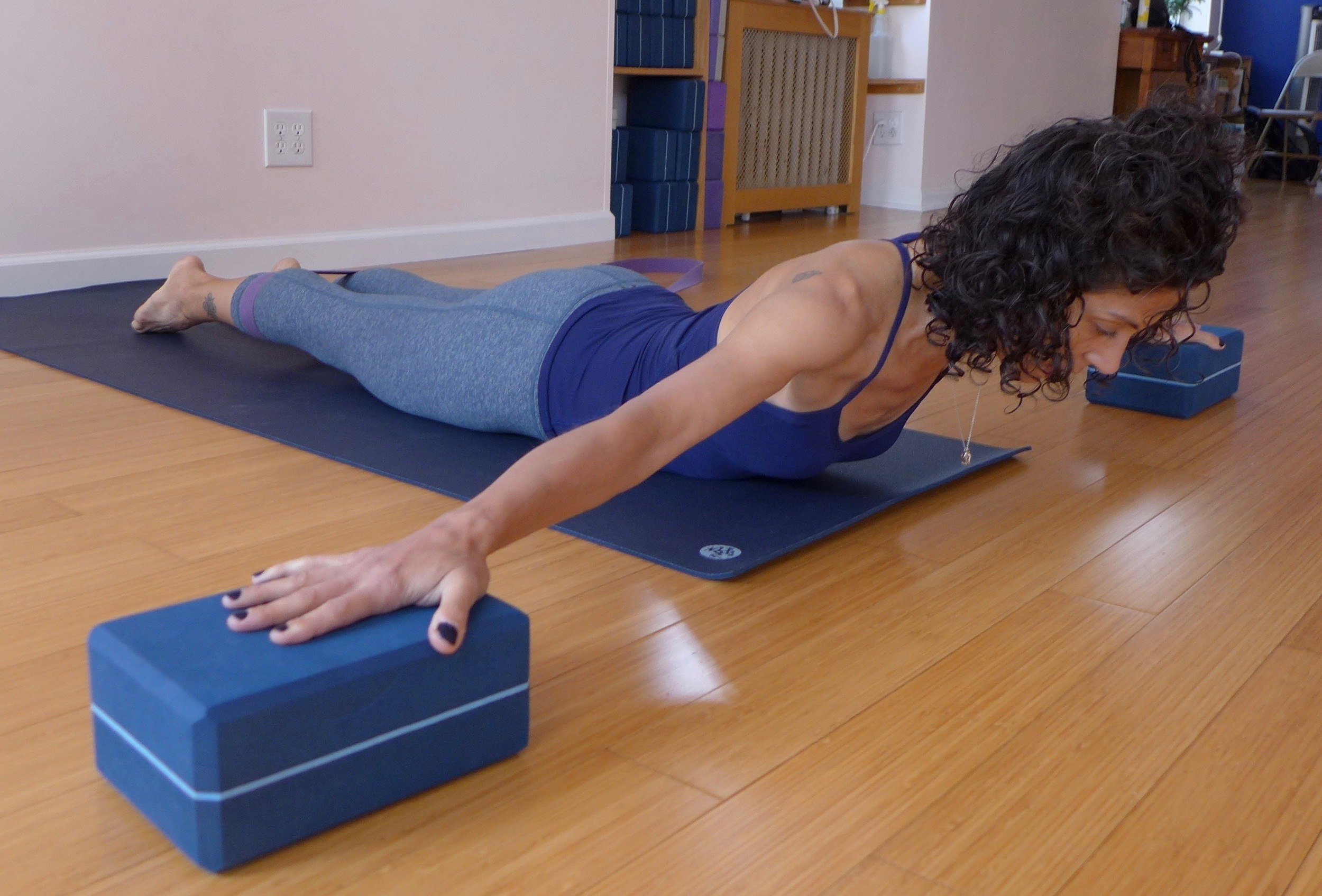 "Cobra pose variation, Part 2: Follow the same key actions as above, just move the blocks off to the sides of your mat and place your arms into a ""t"" shape.  Try to drag the blocks towards you without actually moving them.  This version helps with thoracic mobility."