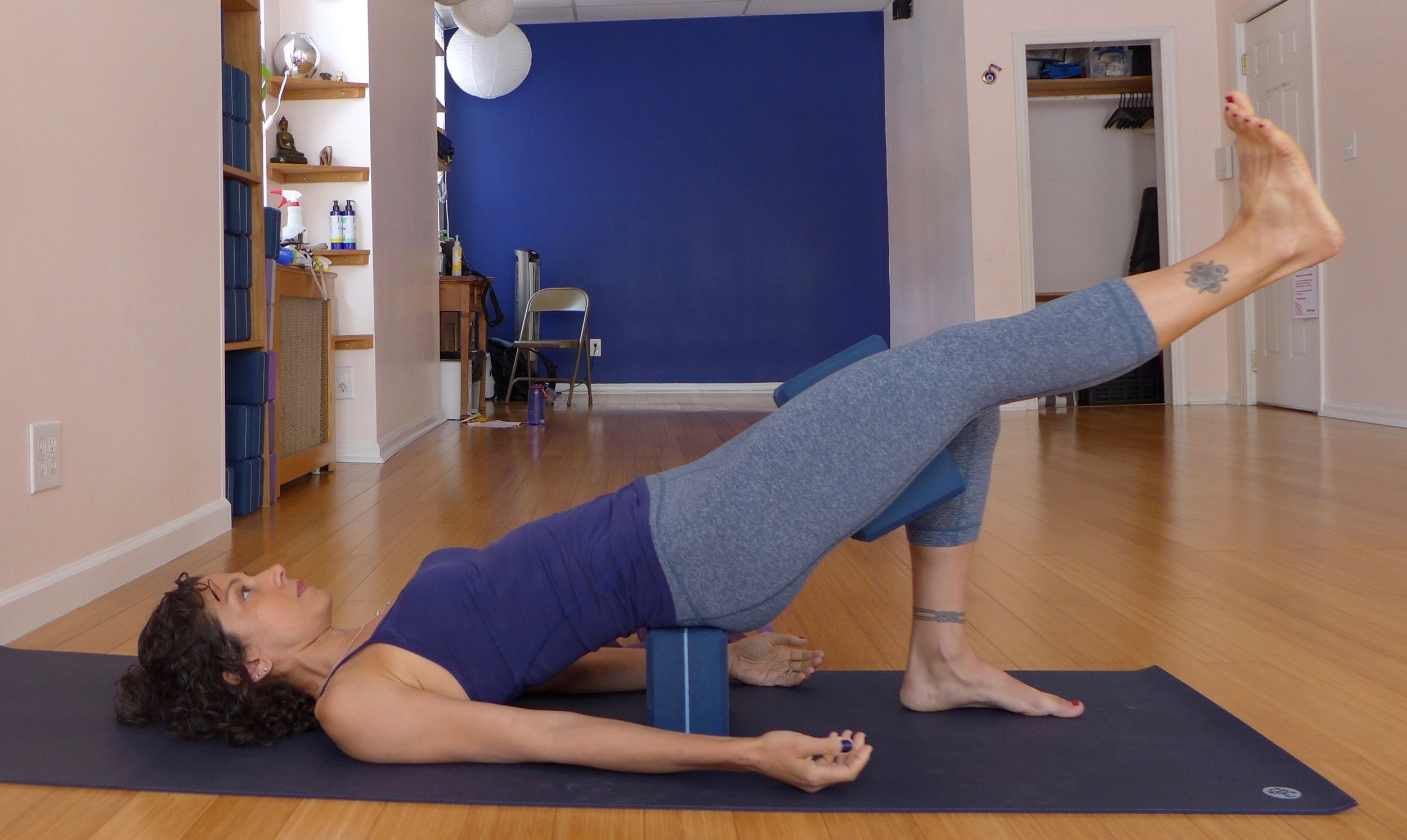 Bridge pose on a block with props: This version of bridge trains pelvic stability from side to side. Place your sacrum on a block, place your pelvis in a posterior tilt.  Press the foot that's on the floor strongly down, which will help engage the hamstring and glute.  Squeeze the block in between your thighs, and lift one leg up.  Keep squeezing the block, and keep your pelvis level  - use your hip points as your guide.  Hold for five breaths, then release, and repeat on the second side.  Repeat both sides three times.