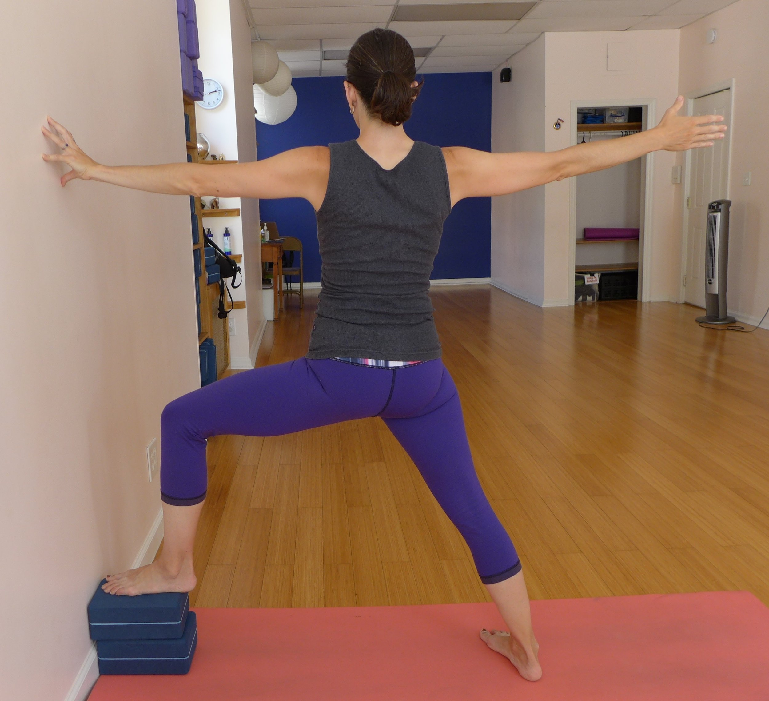 Warrior II at Wall: Warrior II can be a lot for the pelvis after childbirth. I recommend keeping this stance shorter than usual again for 6-24 weeks (or longer) after the birth. Your ligaments are still loose and you want to continue to avoid overstretching them. Here I've put two blocks under the front foot, this can help you get the opening of the inner line of the leg while keeping your stance short. Be sure to engage your outer hips here.