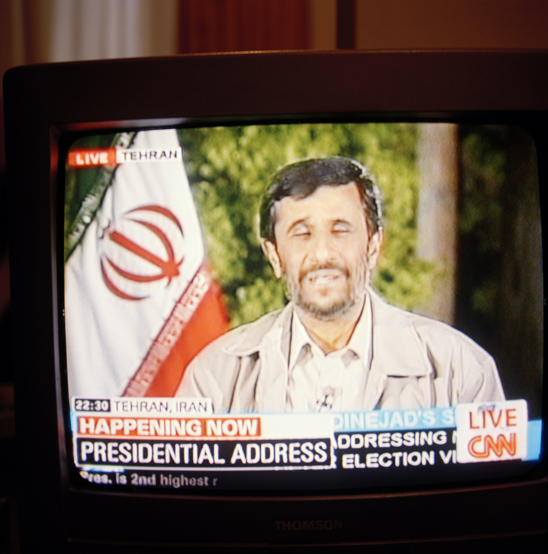 "20:00  With CNN still on the TV, glued to the news coming out of Iran, I watched as Mahmoud Ahmadinejad ""the Iranian George W. Bush"" gave his victory speech. Notice the official time in Iran (22:30) – I had no idea Iran that was 3 hours, 30 minutes ahead of Madrid. I always thought international time zones were separated apart in increments of whole hours. Then I remembered that some countries do that kind of thing. Until I got the film back from the lab I had no idea I had caught with his eyes half shut – how appropriate."
