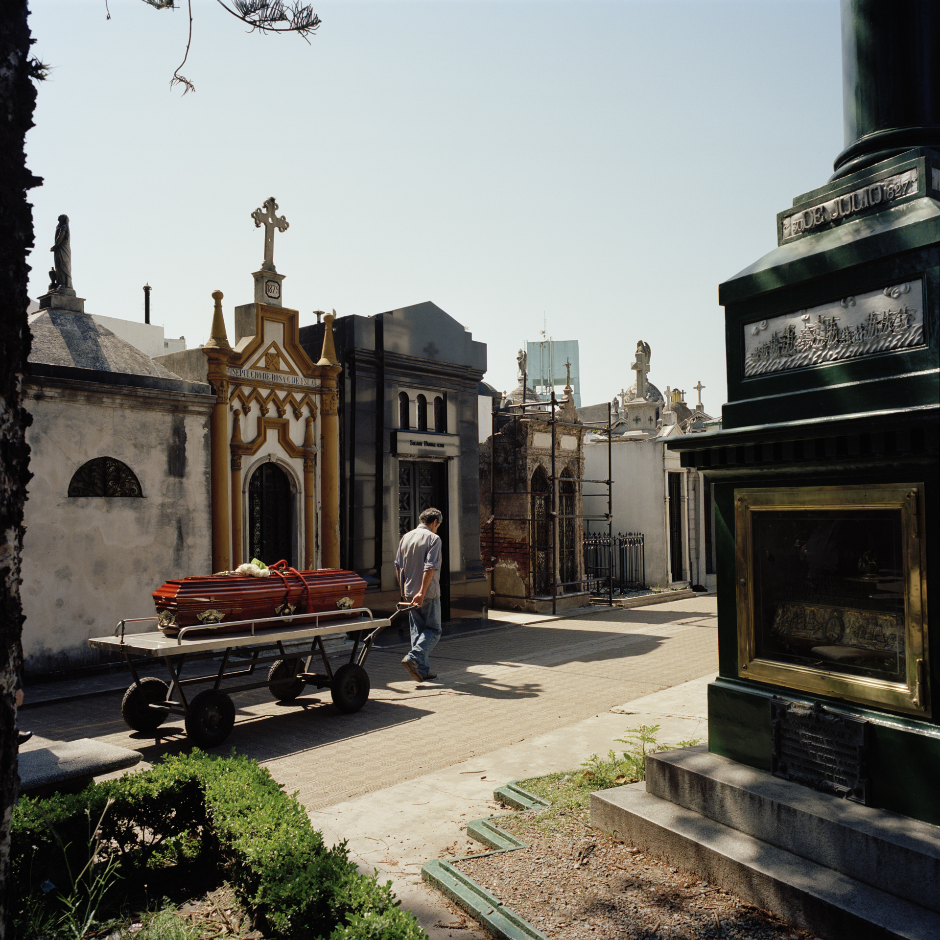 La Recoleta Cemetery. The most well known cemetery in Buenos Aires, where many of the city's most famous and wealthy citizens are buried. A cemetery worker pulls a coffin durig a funeral procession.