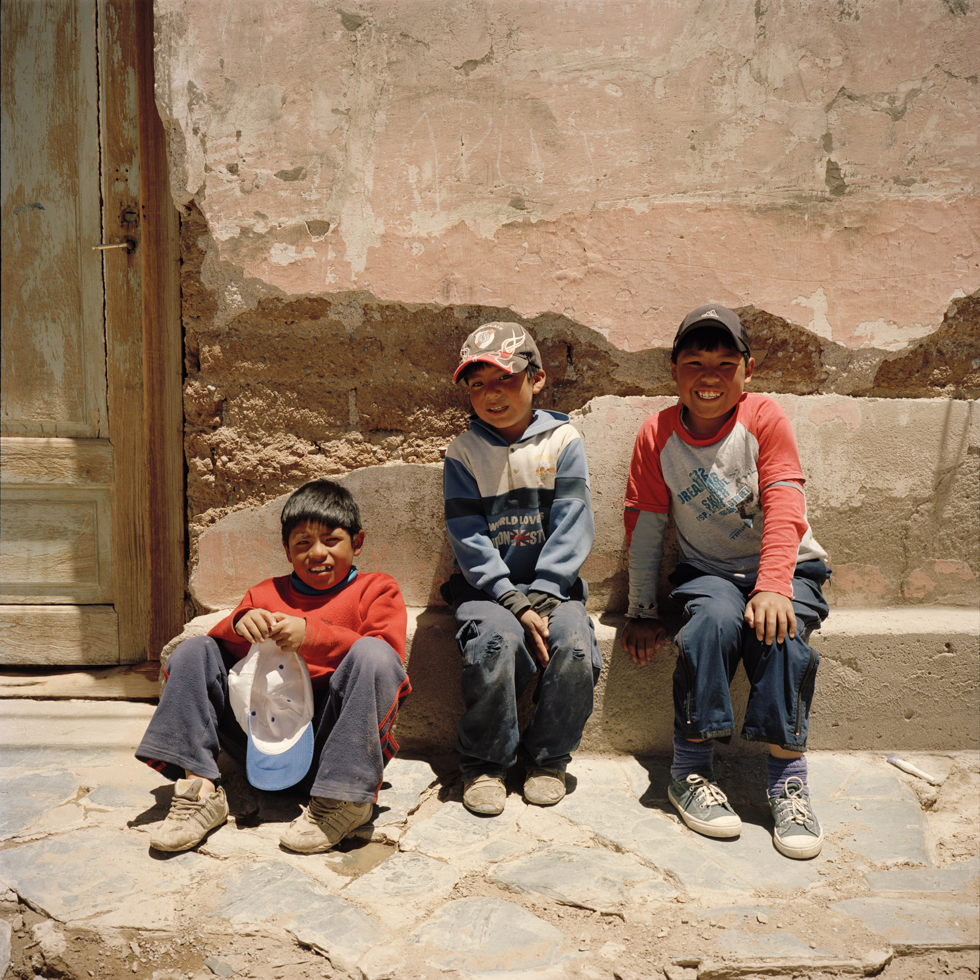 Salta Province. San Antonio de los Cobres. Mining town with 4,200 inhabitants. Boys sit outside a house in the town centre. The elevation at this location is 3,750 meters (12,300 feet), one of the highest of any city or town in Argentina.