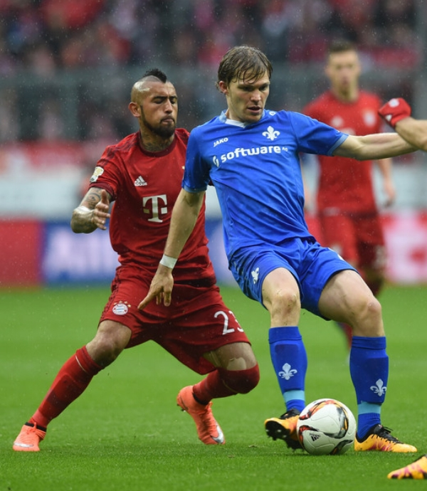 Bayern Munich's Arturo Vidal and Darmstadt's Florian Jungwirth vie for the ball during a German Bundesliga first division match in Munich, Germany.
