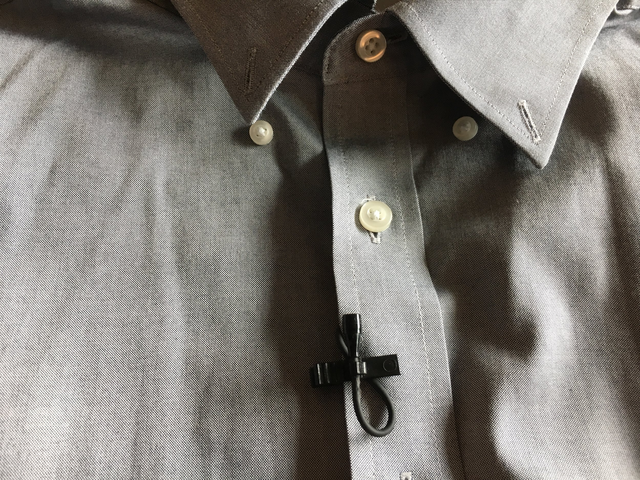 If you are miking a button up, clip the mic with the cord sandwiched under the clip with the mic facing up towards the mouth.