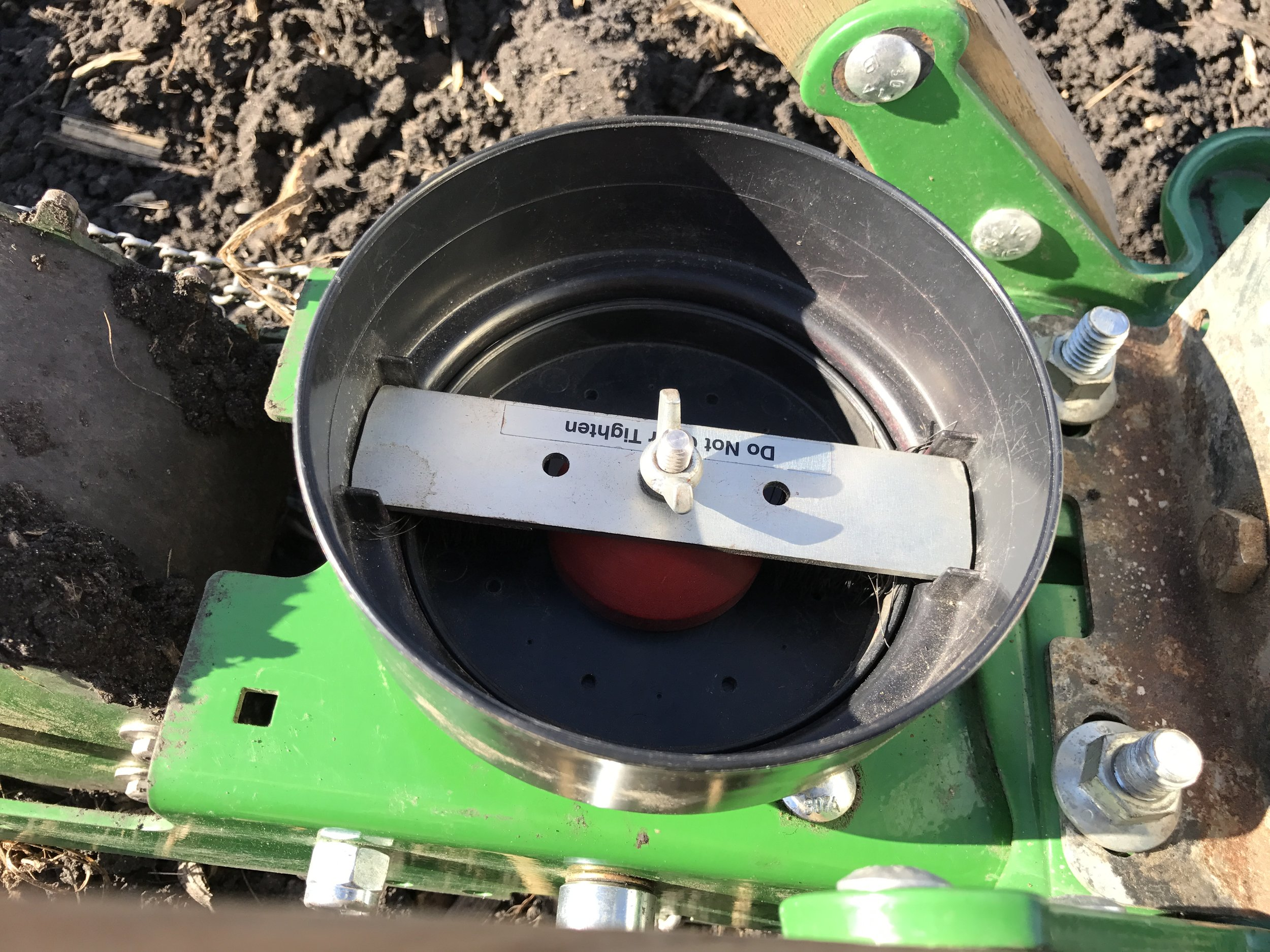 This is our garden seeder without seed. If you look closely you can see holes in the seed plate which will receive seed, space them accordingly, and drop them into their row.