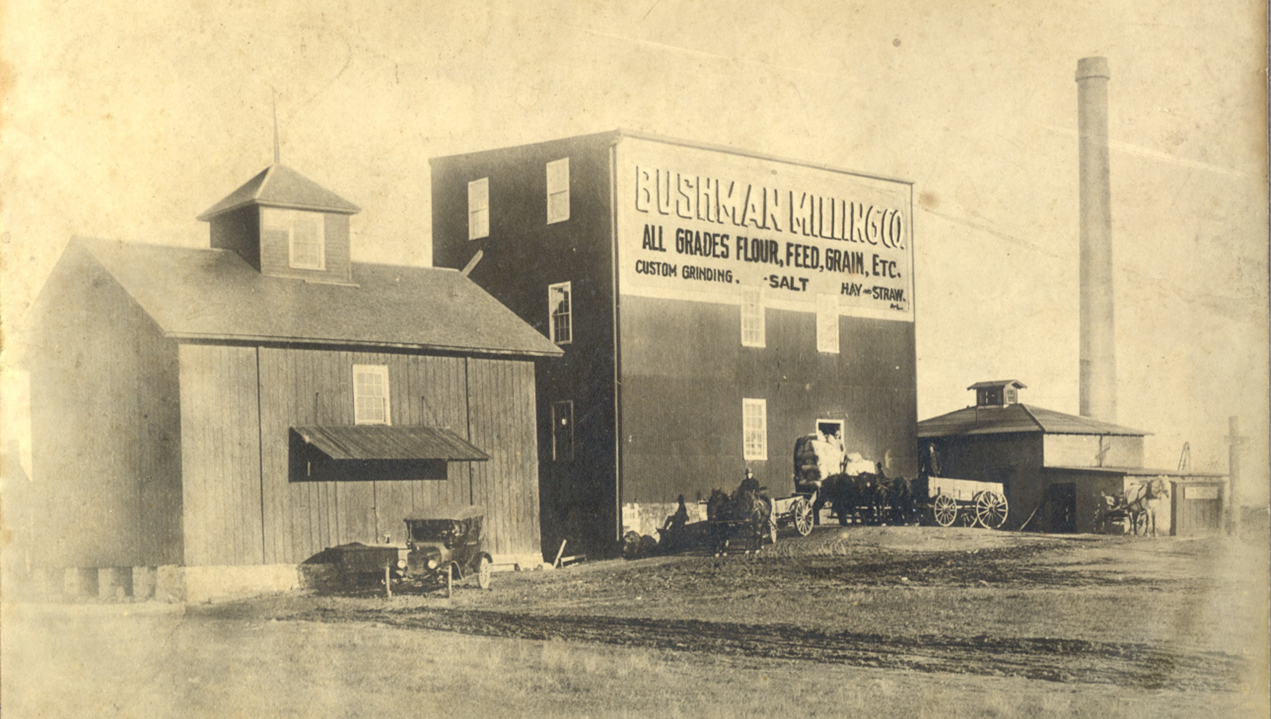 """The Bay View Roller Mill was established in 1885 by Charles Whiteside, L.C. Thorkildson, & A. Shaw on what was then the shore of the bay. In 1899 the adjoining granary on the left was brought to this site by water from Little Sturgeon in the southern part of Door County. The picture (ca. 1920) shows the mill when it was operated by the Bushman Milling Co.  A mainstay of the Sturgeon Bay waterfront during the late 1800's and first half of the 20th century, the mill buildings were removed after the city acquired the property in 1975 for parkland. They stood in what is now the parking lot for the Sawyer Park Boat Launch."""