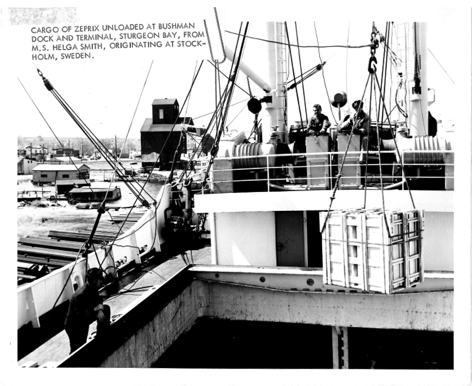 This photograph shows a ship unloading at the Bushman Dock (the next dock over from Teweles & Brandeis' Sawyer Dock). The Teweles & Brandeis elevator is visible in the background. In fact the Lyons Bros. elevator is also shown behind and to right of the Teweles & Brandeis elevator. Estimated circa 1950s.