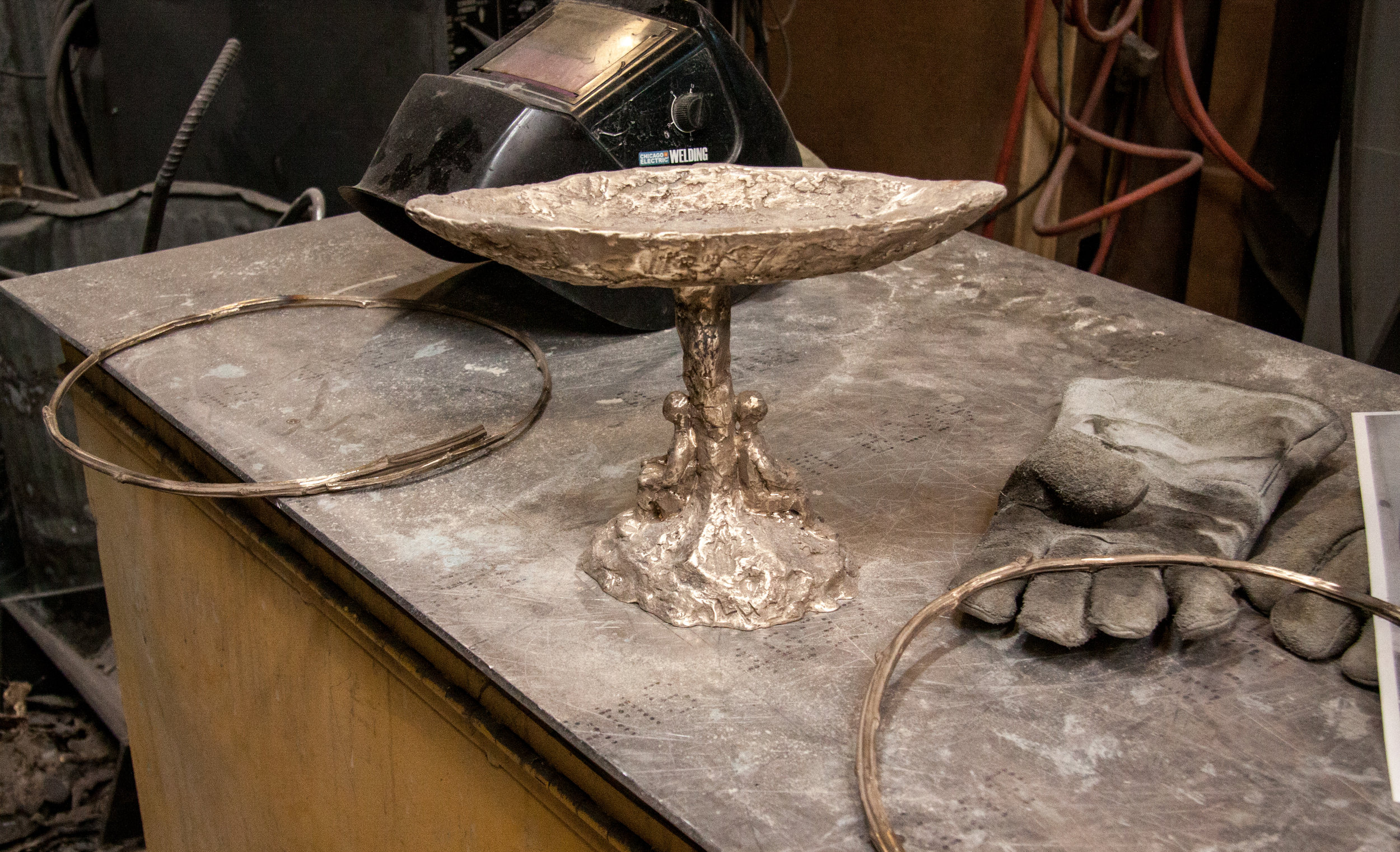 The two circular tree branches will be welded to the sculpture to form the two circles surrounding the chalice flame.