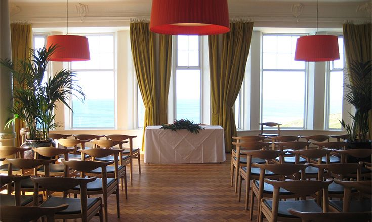 The Dining and ceremony Hall at the Polurrian Bay Hotel is a lovely wood floored room with sea views.