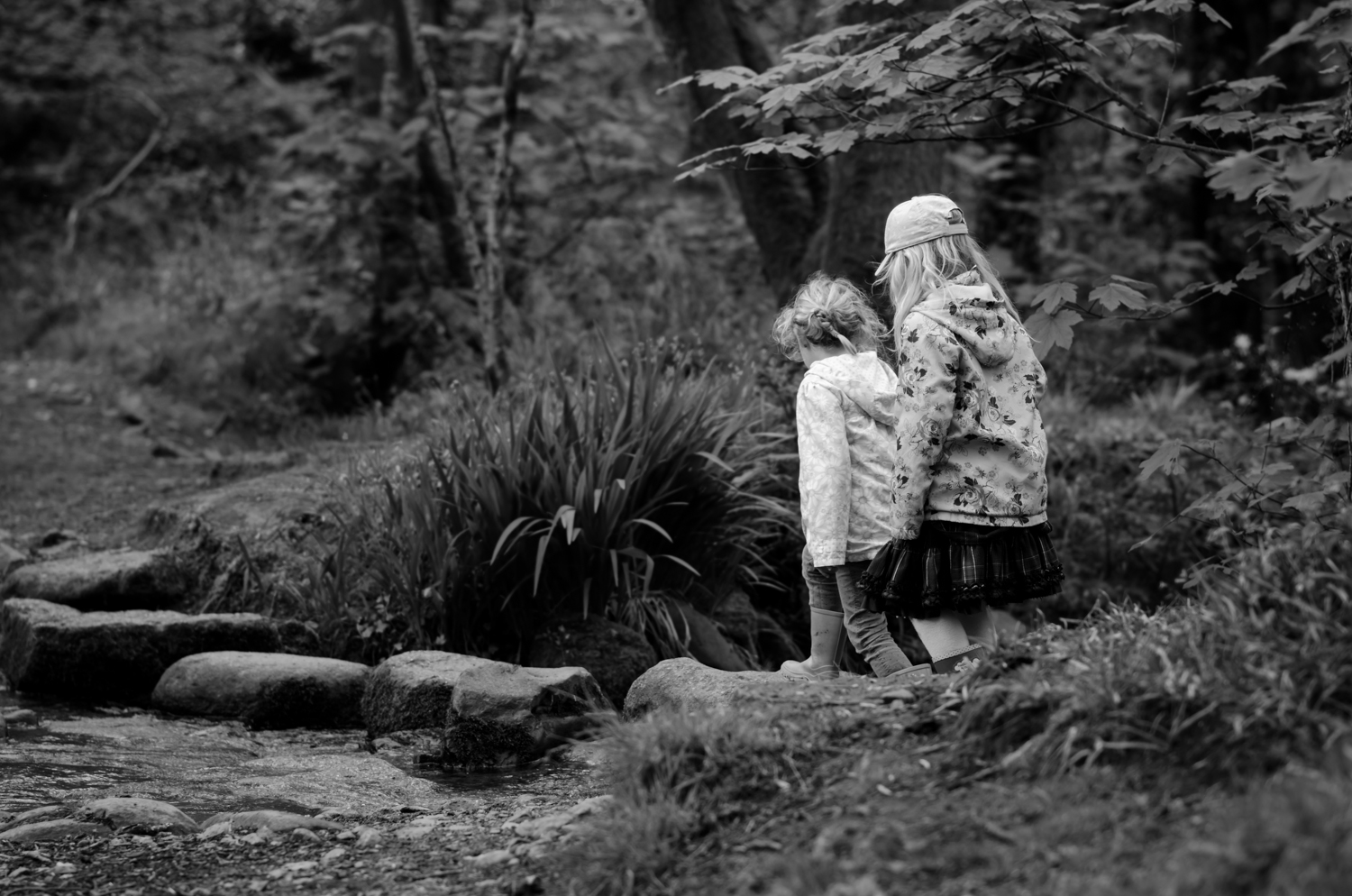 two girls crossing the stepping stones down lower town woods Helston