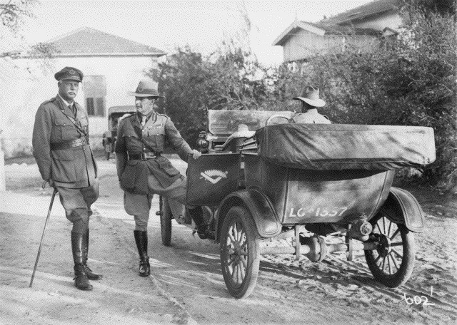 Figure 3: Major General Chaytor with Brigadier General Cox, who is about to step into a car. The formation sign on the door is a silver fern over an upturned boomerang. Reference: Australian War Memorial, ID # B00602.