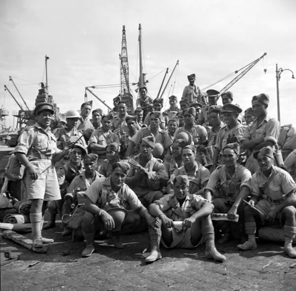 Figure 4: Padre Wi Tetau Huata leading members of the Māori Battalion in a song, while waiting in Alexandria, Egypt, to embark for Italy, 23 October 1943. Source: Alexander Turnbull Library, War History Collection (photographer: M D Elias), reference # DA-08835-F.