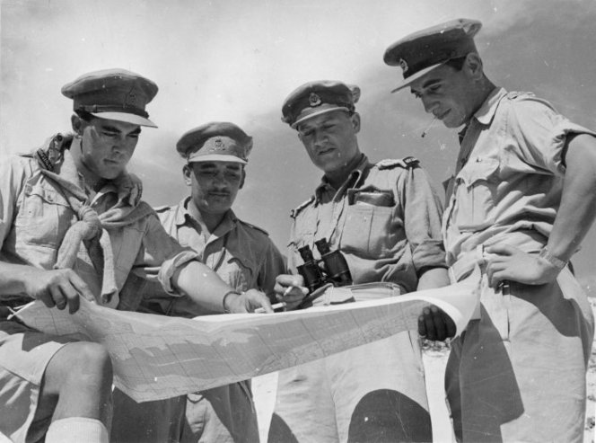Figure 3: Behind the El Alamein front, on the eve of the successful offensive which commenced on 23 October 1942, a group of 28th Māori Battalion officers study a map of the Western Desert. Captain Hēnare is third from left. Source: National Library of New Zealand (Photographer: M D Elias), reference # DA-06727-F.