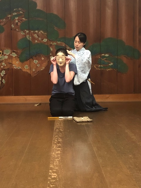 Kimberly, assisted by Oshima Kinue, preparing to practice the shimai  Yuya  with an  Onna  mask, on the practice stage of the Oshima Noh Theatre in Fukuyama.