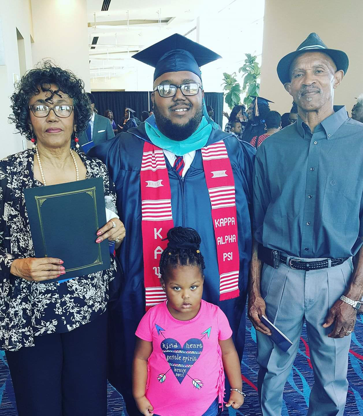 Daisy lee, lorenzo lewis, sareya and t. royal lee celebrate as lorenzo receives his Master's degree.
