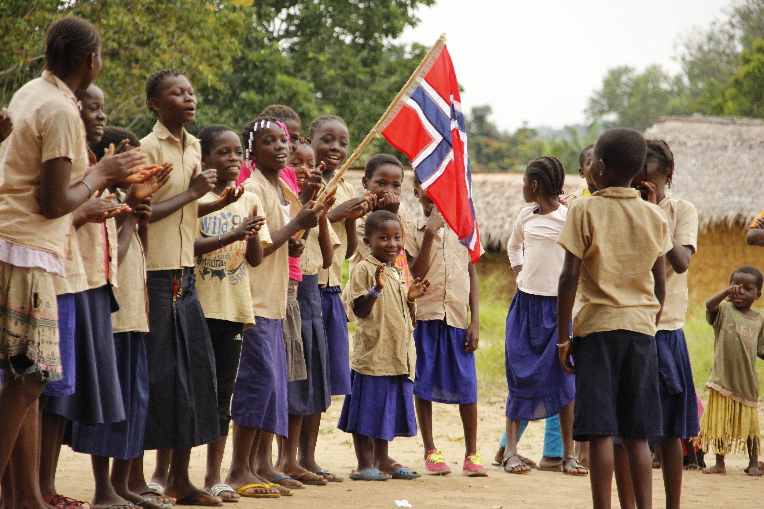 Barn av bantuer og urfolket feirer den store dagen under grunnsteinsnedleggelsen til den nye skolen i landsbyen Onianva.