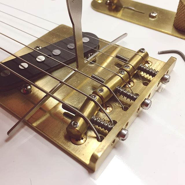 """Setting the string height to match the curve of 10"""" diameter fretboard ... before realising the intonation (whether you're exactly an octave higher at the 12th fret) was considerably flatter than it should be. You can see the saddles (the brass cylinders the strings sit on) are far too close to the back of the bridge plate. Easing the three spring wrapped screws moves the saddles towards the nut, in this case by about 6 or 7mm, shortening the string and raising the intonation from flat to spot on. I've also been working the headstock end, filing the string guides on the nut to leave a gap between string and first fret - when the string is held down at the third - that accommodates the thickness of a folded piece of paper and no more. As always I'm not quite there yet but once done the action (or experience) of playing this guitar should be just so. Guitar number two, and first Rascal Tele, nearly done? Sure is 😎"""