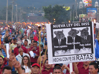 """Photo caption: In the torchlight march in Tegucigalpa. Sign reads, """"New IHSS law made with faith of a rat."""" Photo by Luis Mendez"""