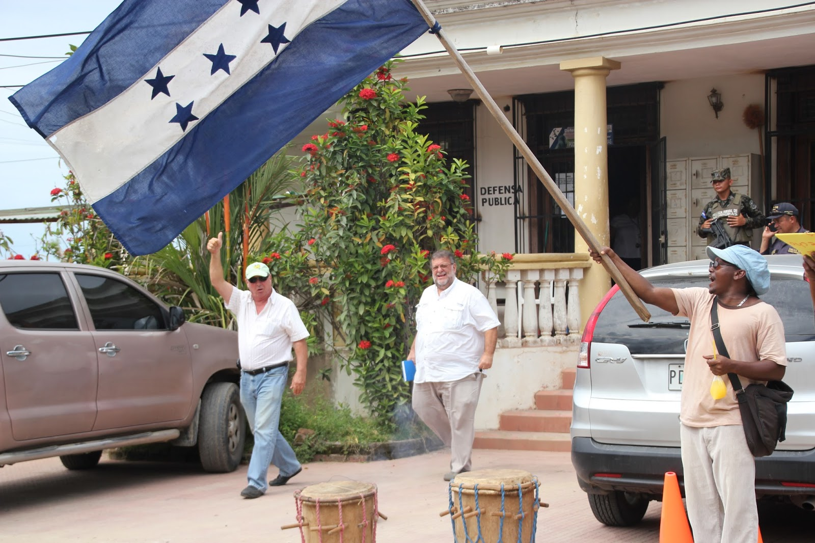 Photo caption: Randy Jorgensen (left) waving obnoxiously to the Garifuna community waiting outside the courthouse to hear the results. Hernan Batres (middle), the General Manager of the cruise ship terminal constructed by Jorgensen's second company in Trujillo, Banana Coast, accompanied Jorgensen to the hearing.