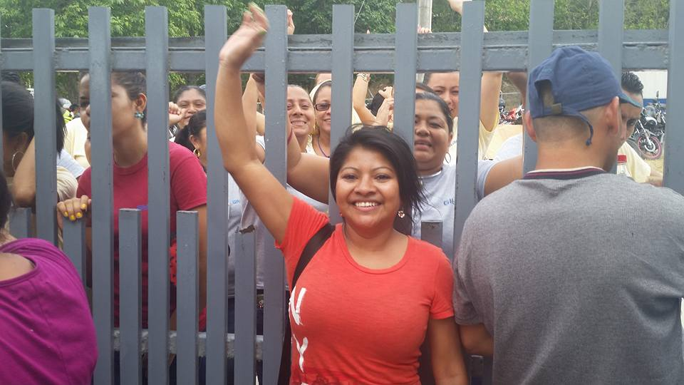 Photo caption: Lilian Castillo after being reinstated outside the gates of Gildan's 'San Miguel' factory in Choloma. Women workers behind her inside the gates show their solidarity on their lunch break. Photo by CODEMUH