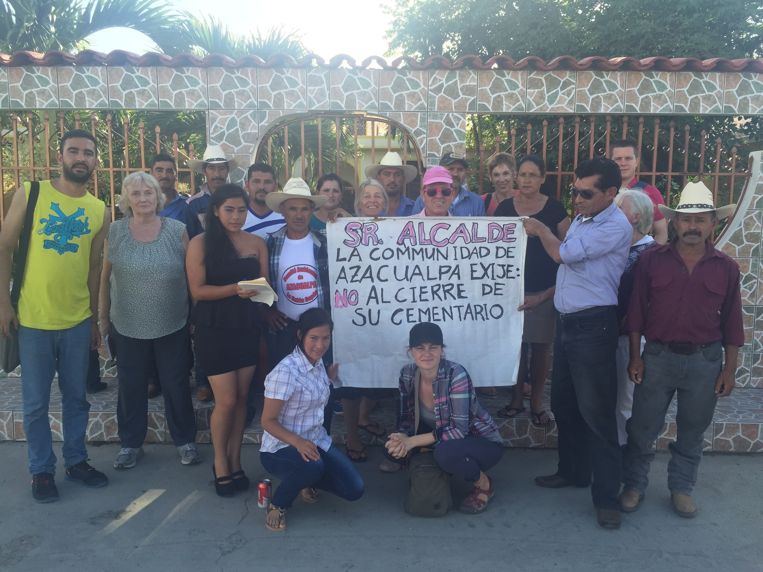"""In front of the house of the mayor of La Unión, Copan with community members and environmentalists from the community of Azacualpa that are fighting to protect their 200-year old cemetery under threat by the expansion of Canadian mining company, Aura Minerals. Sign reads: """"Mr. Mayor. The community of Azacualpa demands: no to the closure of their cemetery."""""""