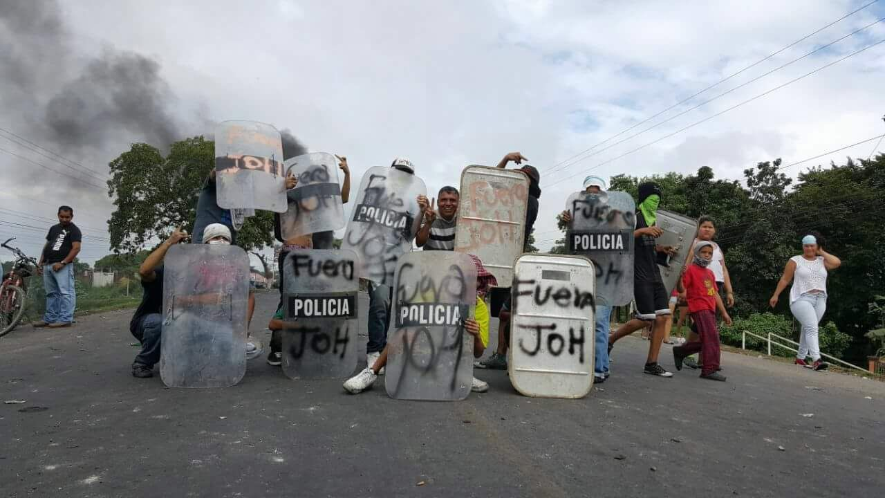"Protesters in northern Honduras take the shield away from the police and decorate them with ""Fuera JOH"""