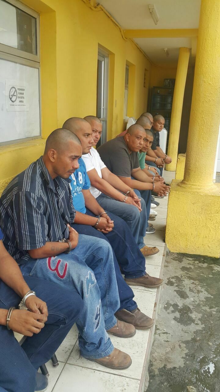 Some of the 11 people arrested in Pimienta, Cortes as retaliation against the local population. The men are waiting outside the courthouse in San Pedro Sula for their initial legal hearing.Their heads were shaved and they were sent to a new maximum-security prison modeled off US-style prisons. Picture by: Unknown.